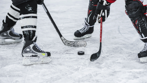 Close Up of Hockey Puck Between Two Players