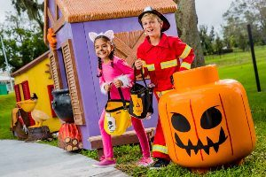 Girl and Boy in Halloween Costumes next to a LEGO Pumpkin at LEGOLAND Brick Or Treat in Central Florida