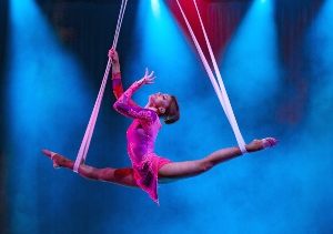 Aerialist in pink costume doing a split on the silks in the air