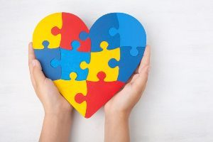 Child's hands holding an autism puzzle heart
