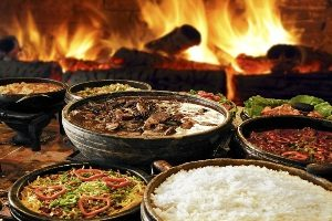 Table of Brazilian food including feijoada and white rice