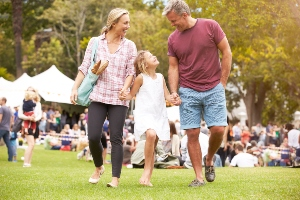 Family at outdoor festival carrying bread and laughing together