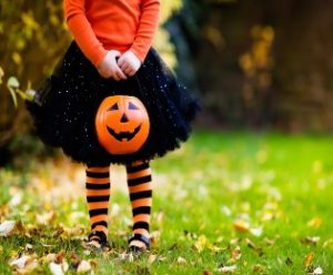 Young girl carrying jack-o-lantern candy basket